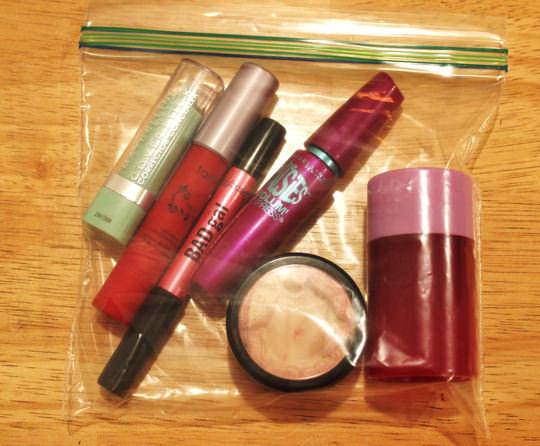 L-R: concealer, red lipstick, black eyeliner, mascara, powder, blush stick