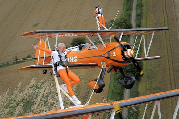 Image: Nine-year-old cousins Rose Powell and Flame Brewer wingwalk over Rendcomb airfield in Gloucestershire
