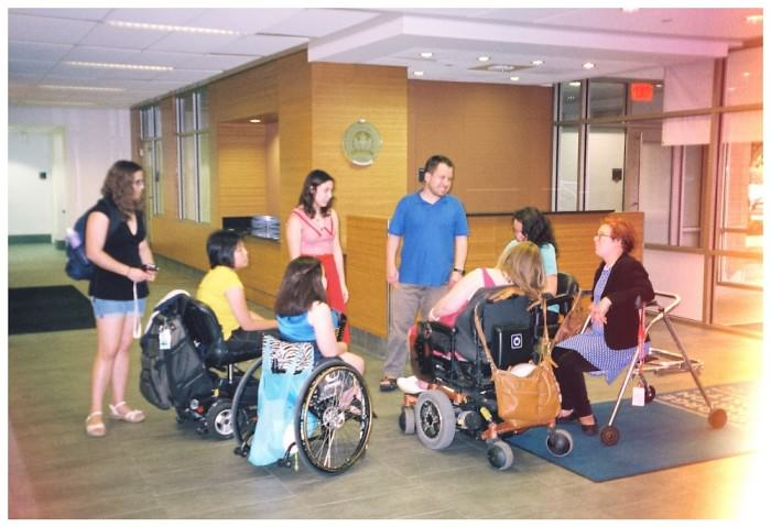 Eight young people wearing colorful, casual clothing congregate in a circle in the lobby of a dorm. Three are standing, two are using scooters, one is using a manual wheelchair, another one a power wheelchair, and one is sitting on a walker.