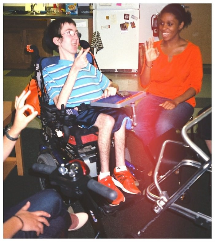 A young man using a power wheelchair teaches the ASL alphabet to a young woman sitting on a plastic chair. He is wearing a blue-and-white striped shirt and blue basketball shorts; she is wearing an orange top and jeans.