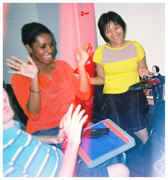 Three people are laughing together. From left to right: a young man in a blue-and-white-striped shirt; a woman in an orange shirt and jeans, holding her hands up and open; and a woman with short black hair in a yellow T-shirt.