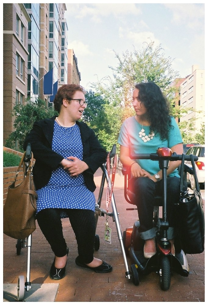 Two young women are stopped on a sidewalk, talking. The one on the left has short red hair and glasses; she's wearing a blue dress with white polka-dots, a black cardigan, black leggings, and flat black shoes. She is sitting on her walker, over which she has slung a big brown handbag. The woman on the right has long black curly hair and is wearing cuffed jeans, a teal T-shirt, white pointed-toe shoes, and a chunky white necklace. She is sitting on her scooter, over which she's slung a massive black bag.