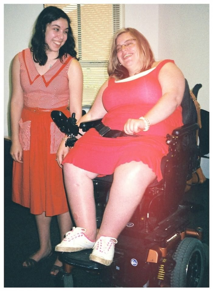 Two young woman laughing. The woman on the left is standing. She has medium-length black curly hair and has on a red-and-white A-line dress with patch pockets, and black sandals. The one on the right is on a power wheelchair. She has shoulder-length blond hair and is wearing a pink tank dress, white sneakers, and glasses.