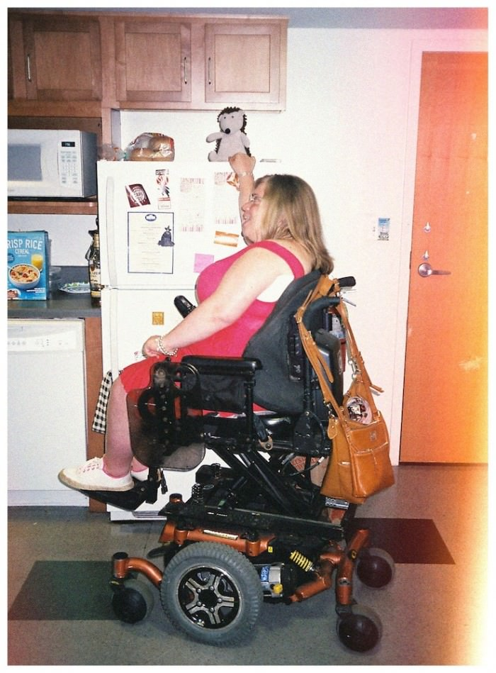 A young woman with shoulder-length blond hair, wearing a pink tank dress, white sneakers, and glasses, is sitting in an elevated power wheelchair. Draped over the back of the wheelchair is a big brown handbag. She is in a kitchen and is reaching up to touch the top of a refrigerator. Sitting on top of the refrigerator is a stuffed animal—a porcupine.