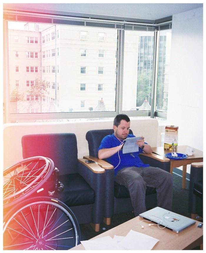 A young man in a blue shirt and gray pants sits on an upholstered chair in a sunny apartment and uses an iPad. Part of a manual wheelchair is visible at the left side of the photo.