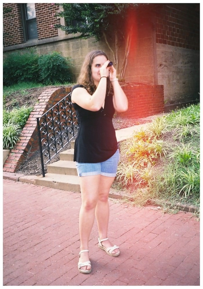 A young woman with curly brown shoulder-length hair, wearing a black shirt and jean shorts, stands outside on a sidewalk, looking at something through a monocular.