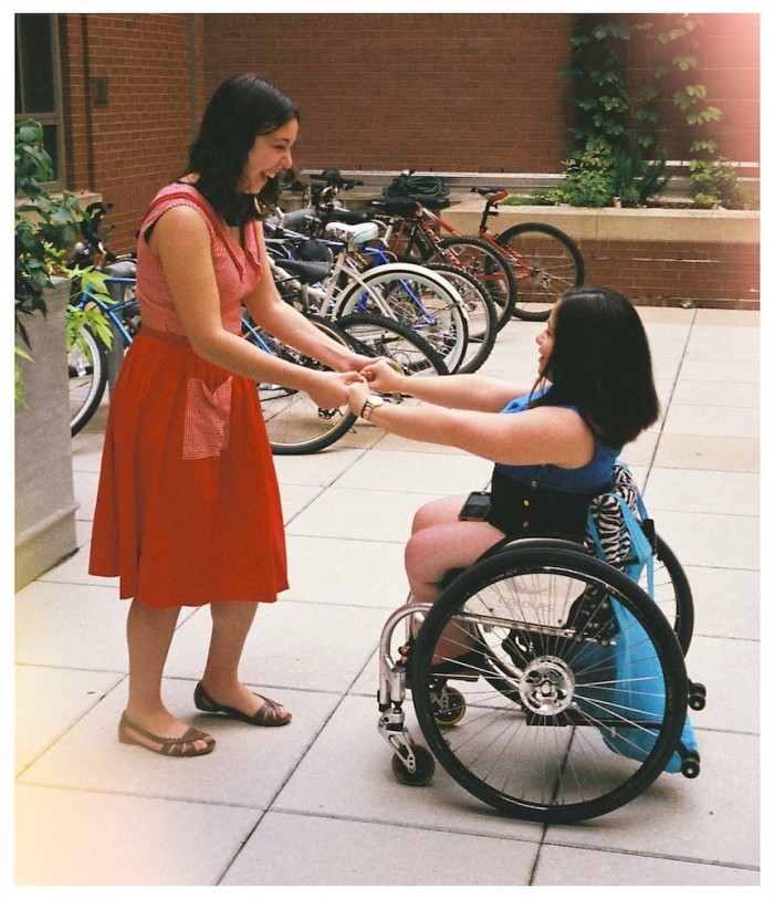 Two young women dancing in a courtyard. One of them, on the left in the photo, is standing up. She has shoulder-length curly black hair and has on a red dress and brown sandals. She's holding hands with the other woman, who is seated in a wheelchair with zebra-print fabric. She has shoulder-length straight black hair and is wearing a short blue dress.