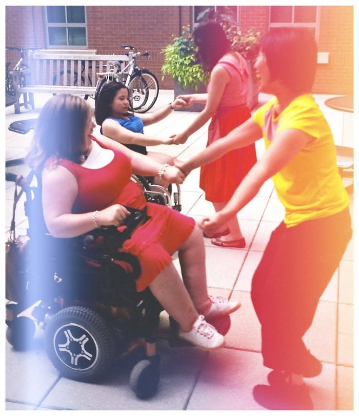Two pairs of young women dancing in a courtyard. In each pair, there is a woman in a wheelchair, holding hands with a woman who is standing in front of her.