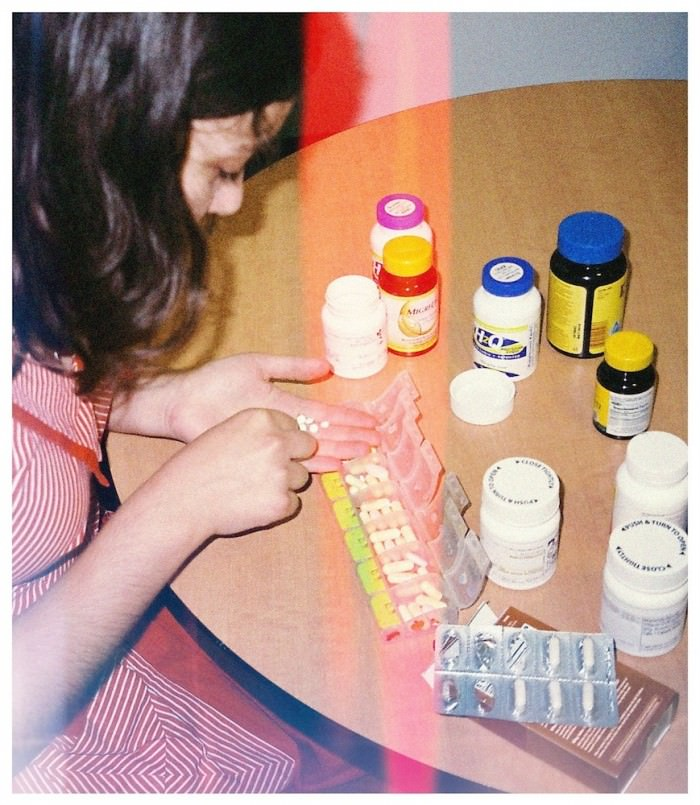 A young woman in a red-and-white dress sits at a table covered in pill bottles and counts out pills to put in a plastic organizer with seven compartments.