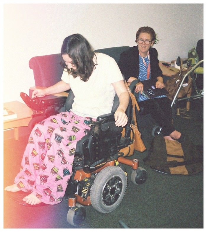 A young woman with dark, wavy hair, in a white T-shirt and pink pajama pants covered in cartoon birthday cakes, is sitting in a power wheelchair. She has one had on the controls and is looking down and laughing. Behind her another young woman, with short red hair and glasses, wearing a blue dress with white polka-dots, looks on, smiling. They are in a living room.
