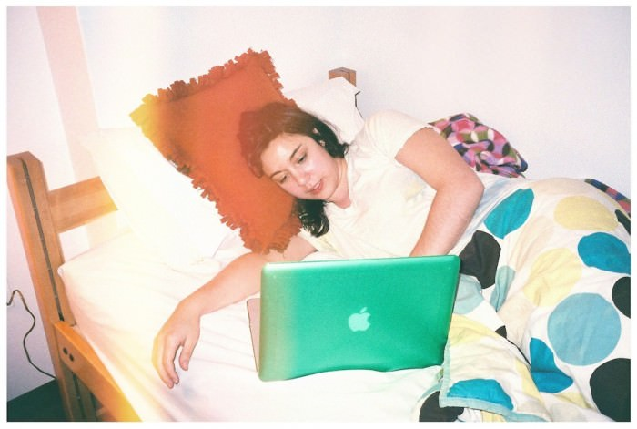 A young woman with shoulder-length black curls lies in bed and uses a Macintosh computer. She is wearing a white T-shirt and is partially covered by a polka-dot bedspread. The case over her computer is green.