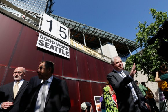 Mayor Ed Murray, far right, after passing a new wage bill in Seattle. Photo by Ted S. Warren/Associated Press via The New York Times.