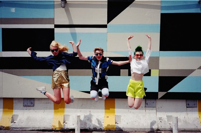 On Kelly (far left): blue top by Band of Outsiders, white tank top by  Theyskens' Theory, leather shorts by Creatures of Comfort, socks by Topshop, sandals by Organic by John Patrick. Kelly's own sunglasses. On Meaghan (center): shirt by Timo Weiland, two pairs of shorts by  Theyskens' Theory. Sneakers and sunglasses, Meaghan's own. On Chloe, far right: shirt by   Theyskens' Theory, shorts by Timo Weiland. Boots and sunglasses, Chloe's own.
