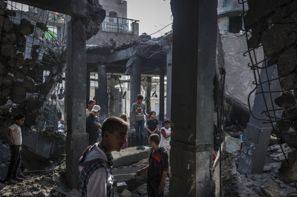 Palestinian boys in a bombed mosque in Gaza. Photo by Sergey Ponomarev for The New York Times.
