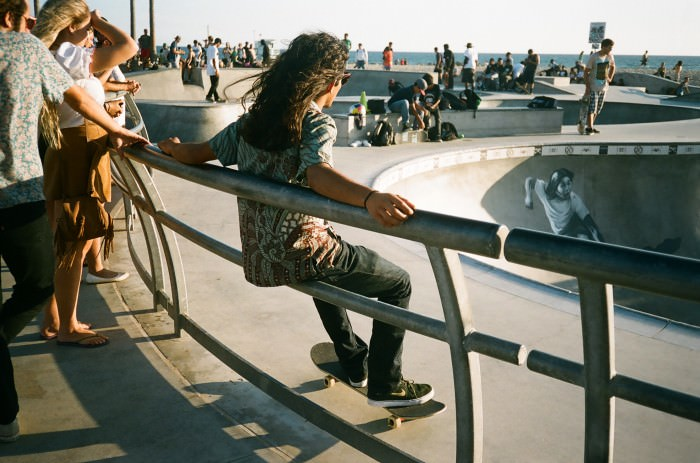 A pretty skater boy taking a break at Venice Skate Park.