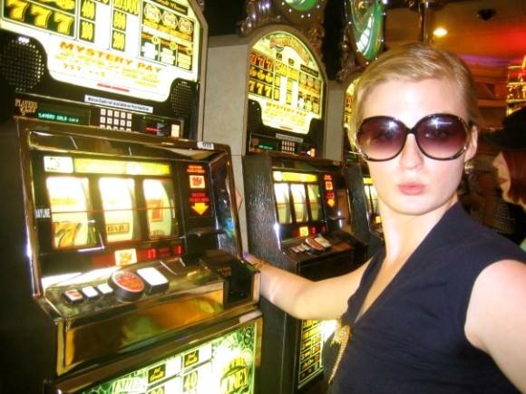 Oh, just another rich grandma in Vegas. Note the deep neckline held together with a giant gold alligator pin, the enormous glasses, and the lipstick worn off from several trips to the casino buffet.